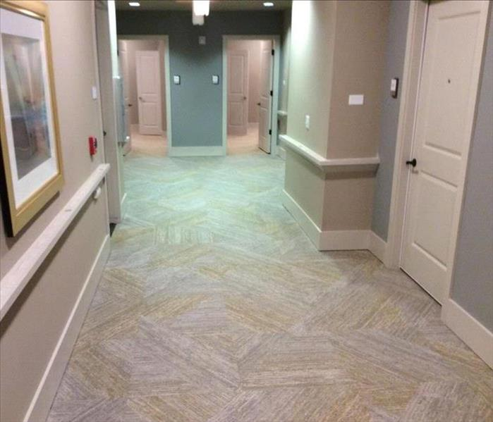 empty hallway with gray and yellow carpet and gray and cream walls