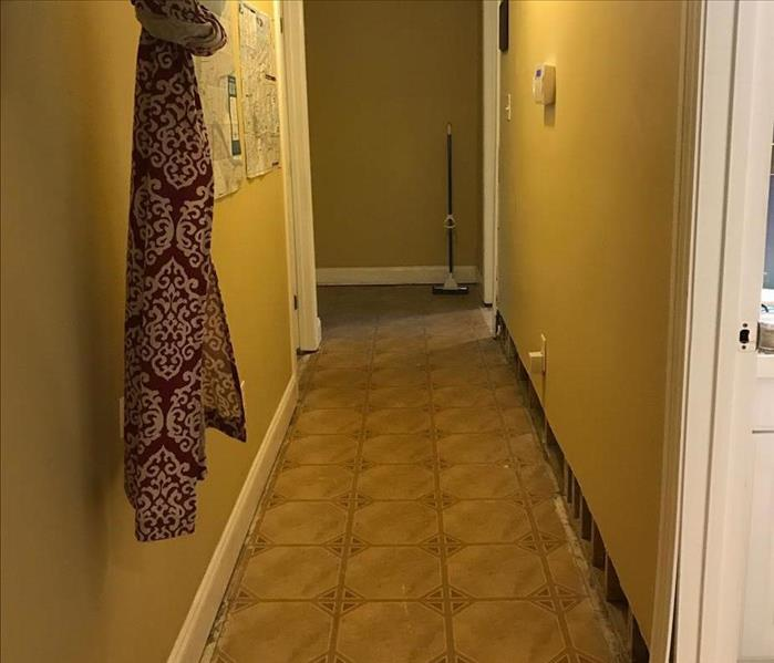 hallway with yellow walls and old small tile flooring and one side of white baseboard removed