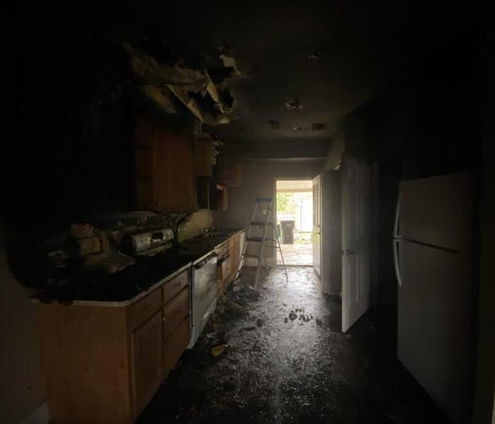 small kitchen badly damaged by fire with all cabinets black from fire and soot
