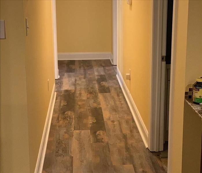 yellow hallway with white baseboards and new engineered wood floording