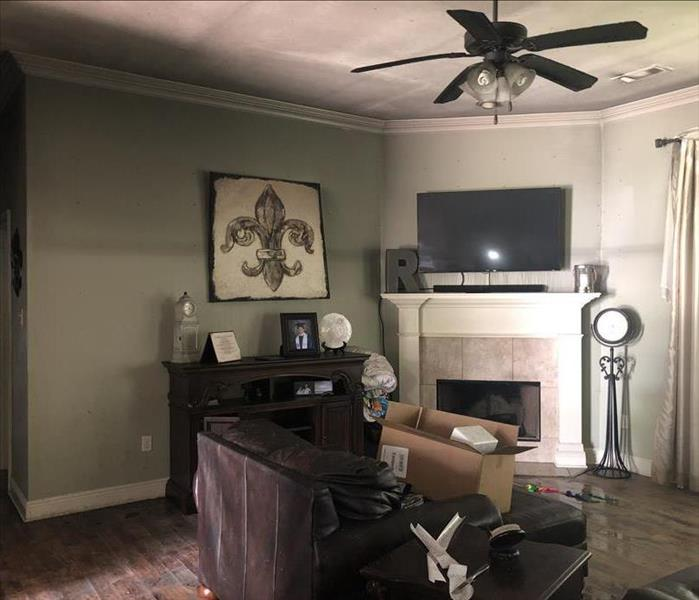 Living room with fireplace, chair, ceiling fan