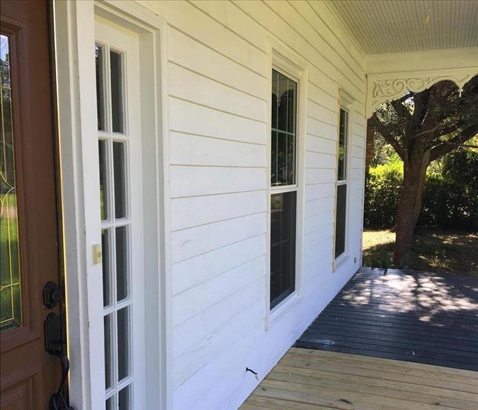 primed white siding on front porch with new wood decking on half