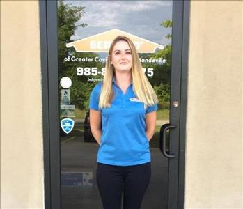 woman with blonde hair standing in front of door wearing blue shirt and black pants