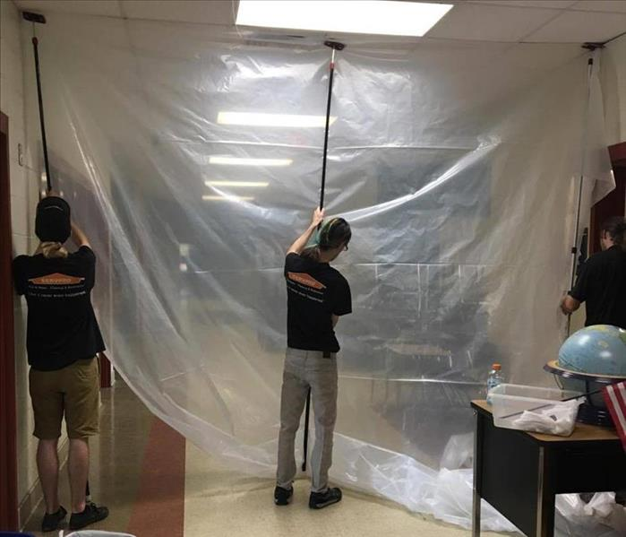 three men in black SERVPRO branded tshirts and khaki pants using poles to set up plastic containment in hallway