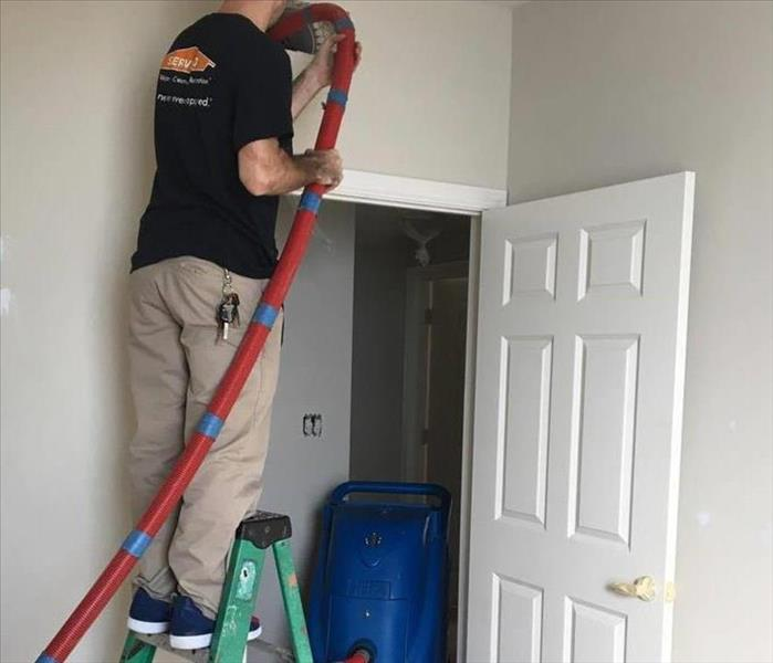 male technician in black t-shirt with SERVPRO logo and khaki pants standing on ladder inserting duct cleaning hose in vent