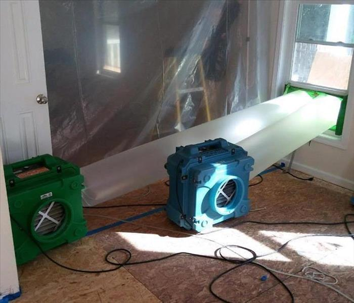 green fan and blue fan with plastic cylinder hoses pumping air our of window