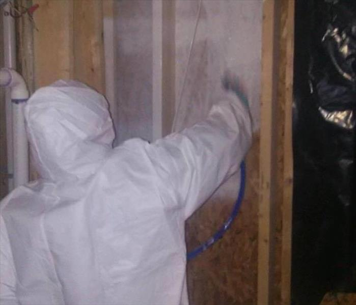 person in white hazmat suit spray white sealer on wall without sheetrock