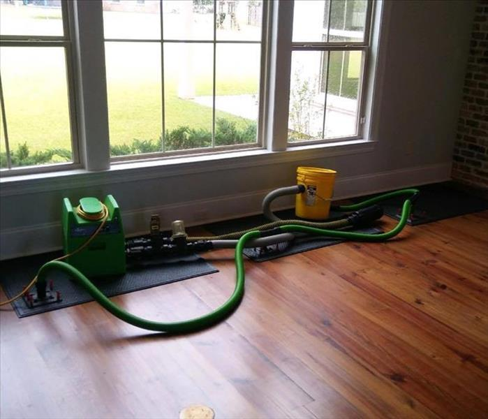 mats and hoses on top of wood flooring with window facing green backyard
