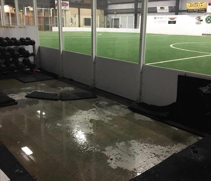 water on ground of indoor soccer field and workout area