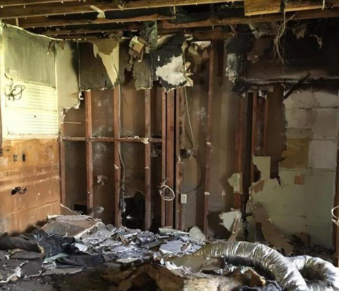 fire damaged room with exposed studs on walls and ceiling with hanging drywall