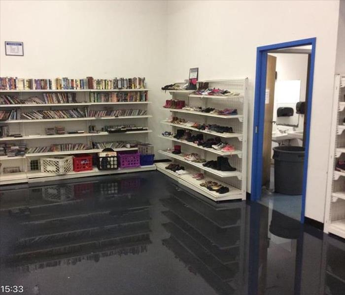 corner of store with book shelves filled with books with water on ground