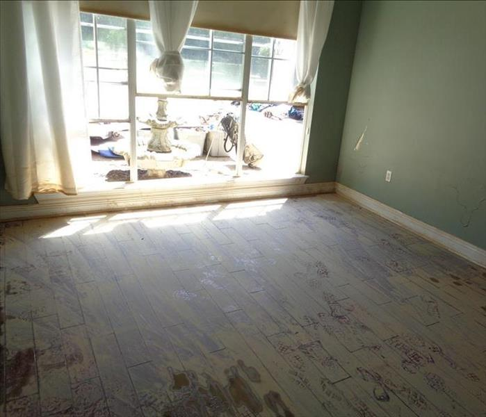 clay and dirt on wood flooring in empty room with big window