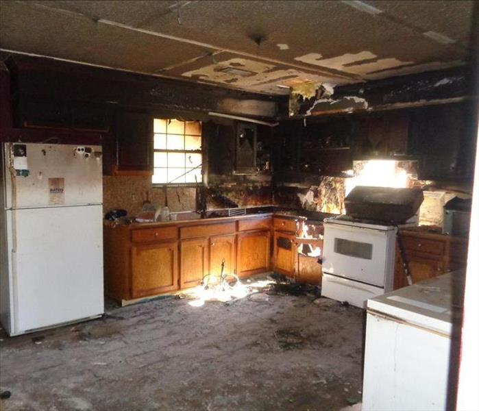 kitchen with white appliances and wooden cabinets black because of fire damage