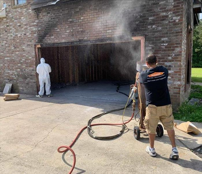 open garage with fire damage on outside brick with two technicians cleaning
