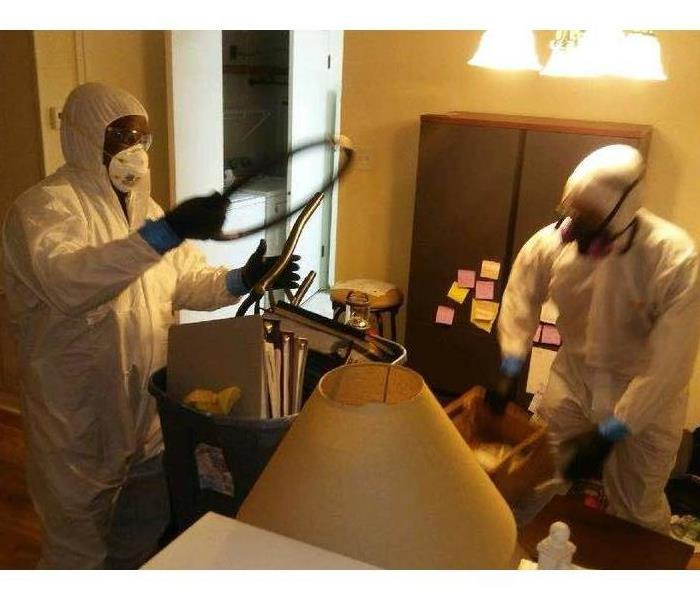 two technicians in personal protective equipment, gloves, respirators, and white hazmat suits, cleaning room