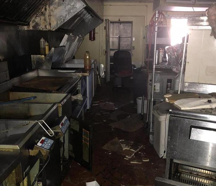 grease covered commercial kitchen with stainless steel equipment cluttered with trash